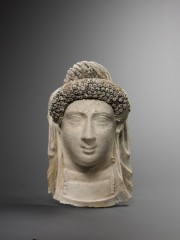 Stucco funerary mask of a female head